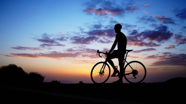 일몰 바위에 자전거 라이더의 실루엣. - mountain top 스톡 비디오 및 b-롤 화면