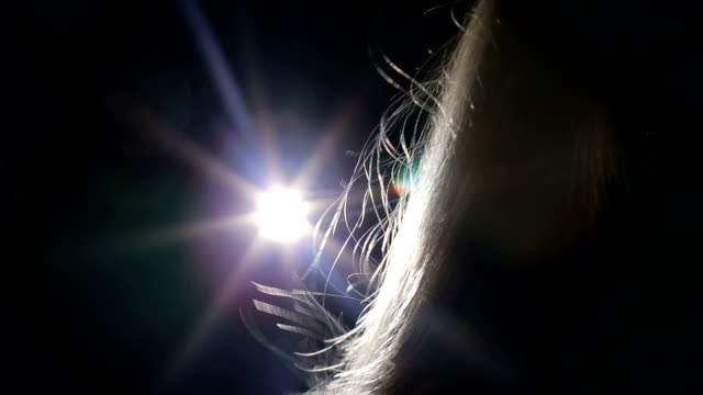 silhouette of blond girl with flying hair in the wind in a long corridor in dark - angelo video stock e b–roll