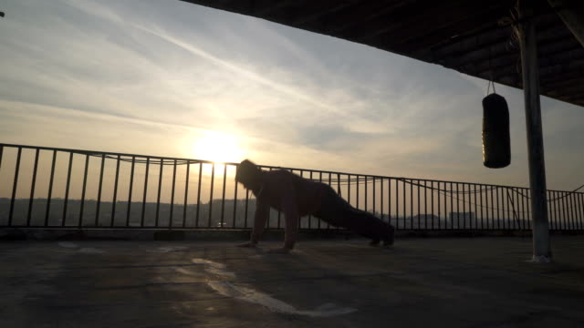 silhouette of boxer while doing push ups with clapping hands on terrace, sunset, sportsman practicing, power training, strong guy hard exercising, strength exercises, workout, handheld, sunny day. - irriducibilità video stock e b–roll