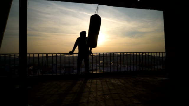 vídeos de stock, filmes e b-roll de silhueta de saco de boxe enquanto balançando, pôr do sol, o homem vem e olhou a cerca, esportista praticando, poder treinar, tipo forte, duro, exercício, exercícios de força, treino, handheld, ensolarado dia. - artes marciais