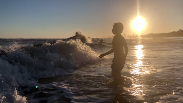 Silhouette of boy at the beach waves crashing