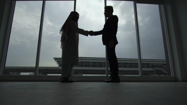 silhouette of business partner shaking hands - arabia saudita video stock e b–roll