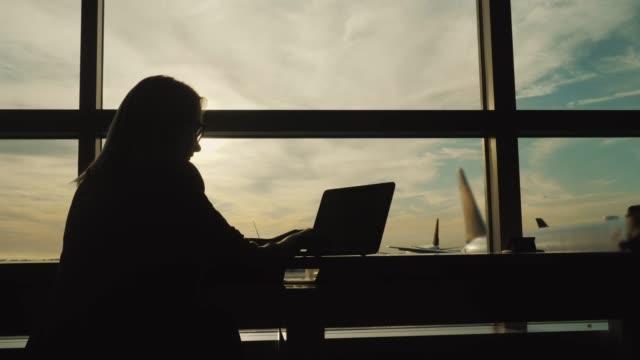 stockvideo's en b-roll-footage met silhouet van zakenvrouw in pak, werken met de laptop in de terminal van de luchthaven - vliegveld vertrekhal