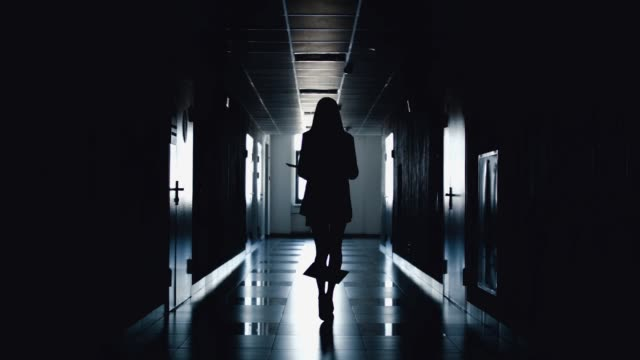 Silhouette of business woman walking along the corridor.