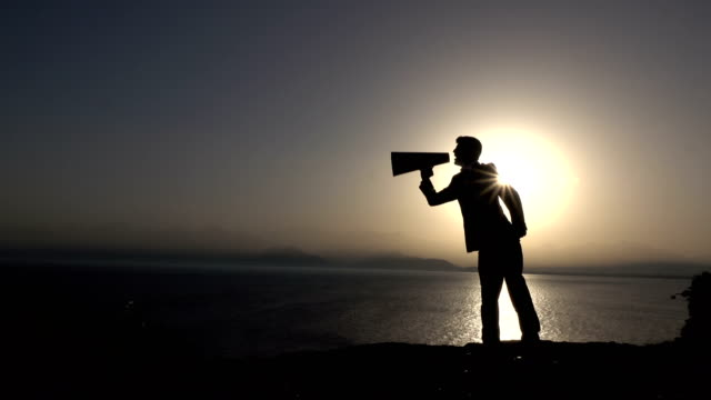 Silhouette Of Businessman Shouting Through Megaphone In Sunset video