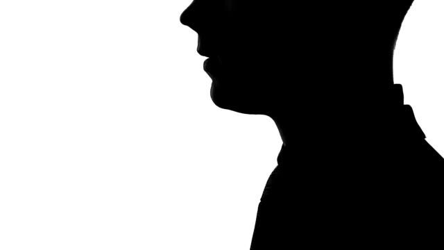 vídeos y material grabado en eventos de stock de silueta de hombre de negocios mostrando el gesto de silencio a alguien, secretos y chismes - dedo sobre labios