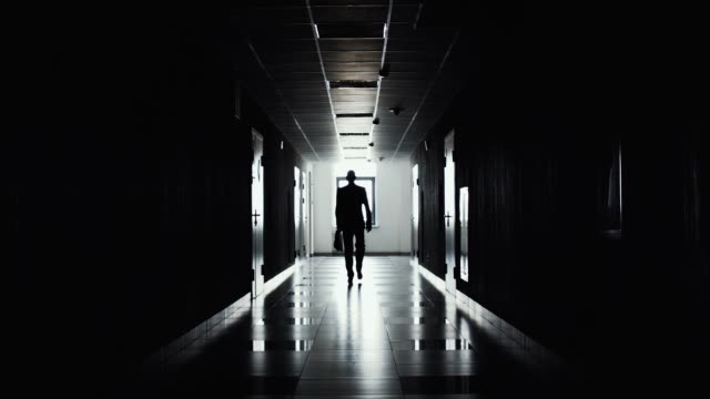 Silhouette of businessman walking along the corridor.