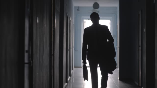 silhouette of businessman with briefcase walking in hallway - completo video stock e b–roll