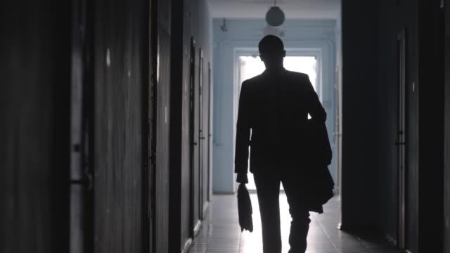 vidéos et rushes de silhouette d'homme d'affaires avec mallette marchant dans le couloir - costume habillé