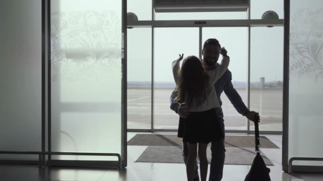 silhouette of caucasian young man entering the glass airport door with luggage. little cheerful girl running up to her father. arrival area, meeting after journey, tourism. - arrivo video stock e b–roll