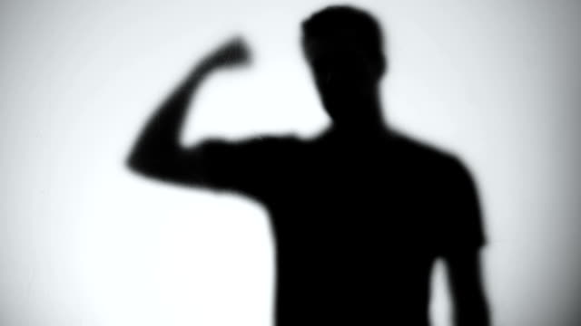 Silhouette of confident man showing biceps, bodybuilding and fitness, close-up