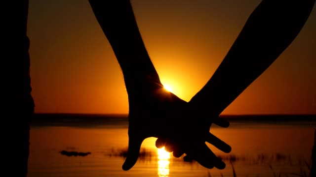 Silhouette of couple joining hands over sunset