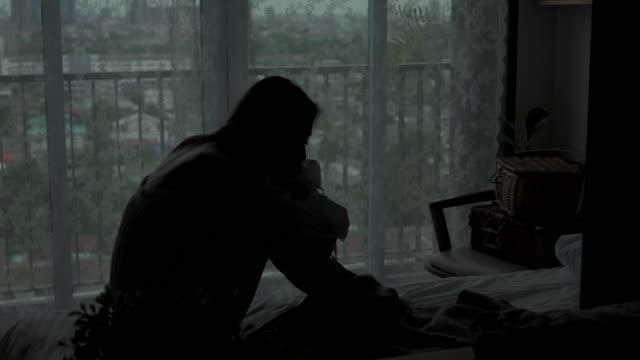 4k silhouette di depresso giovane bella donna asiatica seduta da sola sul letto nella camera da letto dell'appartamento con pianto. la ragazza triste solitudine pensa ai problemi di dolore. emozione negativa e concetto di salute mentale. - violenza donne video stock e b–roll
