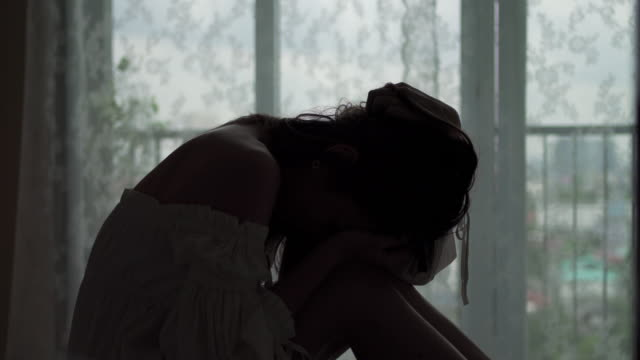 4k silhouette di depresso giovane bella donna asiatica seduta da sola sul letto nella camera da letto dell'appartamento con pianto e urla. la ragazza triste solitudine pensa ai problemi di dolore. emozione negativa e concetto di salute mentale. - violenza donne video stock e b–roll