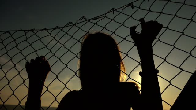 Silhouette of desperate woman imprisoned behind a net video
