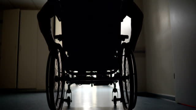 Silhouette of disabled man pushes himself in wheelchair down hospital corridor Silhouette of disabled man pushes himself in wheelchair down hospital corridor wheelchair stock videos & royalty-free footage