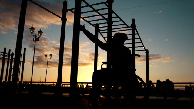 Silhouette of disabled young man pulled up on the crossbars at the sunset outdoors video