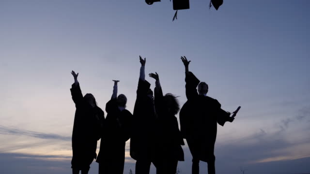 silhouette of diverse international students celebrating graduation tossing caps in the air - struttura pubblica video stock e b–roll