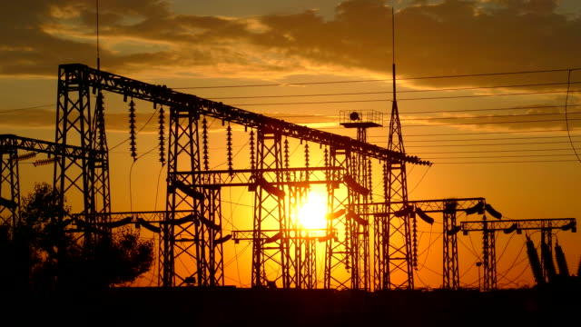 silhouette of electric substation at sunset - sottostazione elettrica video stock e b–roll