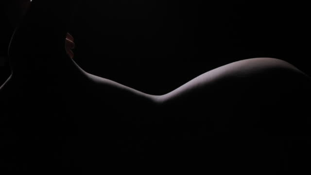 Silhouette of elegant young woman erotic demonstrating her perfect sensual body in dark studio.Portrait,Body.Real Bodies video