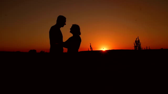 Silhouette of embracing elderly couple at sunset.