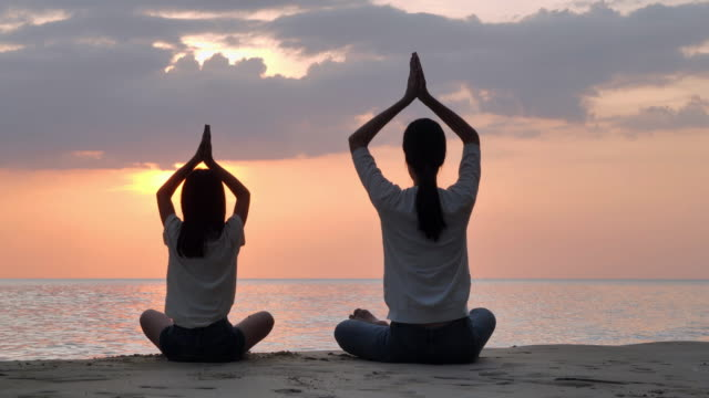 Silhouette of family mother and child daughter are engaged in yoga on a beach in front of beautiful sea on sunset day.Family,People,Vacation,Healthy,Lifestyle,Friendship.Vacations - iStock - vídeo