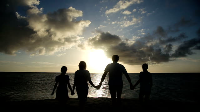 silhouette of family on the beach at sunset video