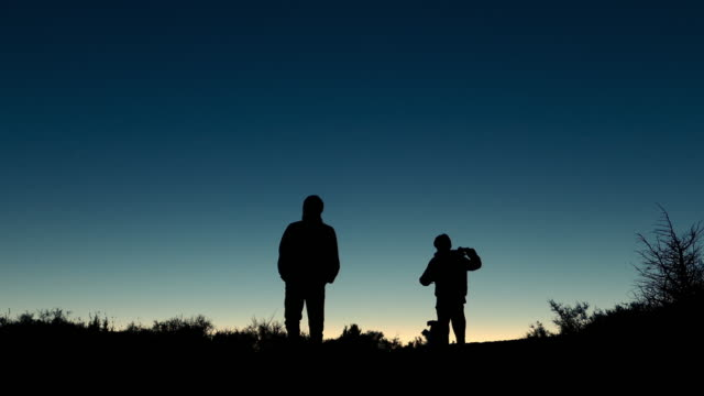silueta de caminata familiar en el campo con un perro al atardecer - vídeo