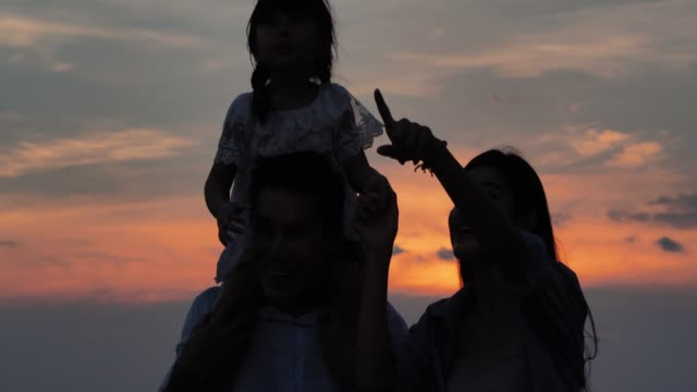 Silhouette of family walking on beach watching and enjoying the sunset.Vacations - iStock