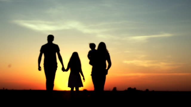 Silhouette of Family Walking Together At Sunset video