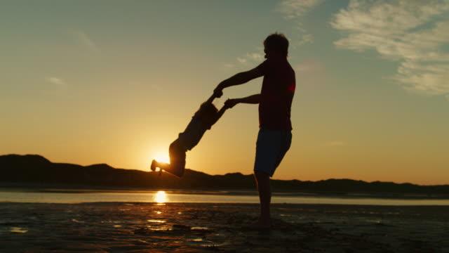 silhouette of father and son playing together at the beach. - samotny ojciec filmów i materiałów b-roll