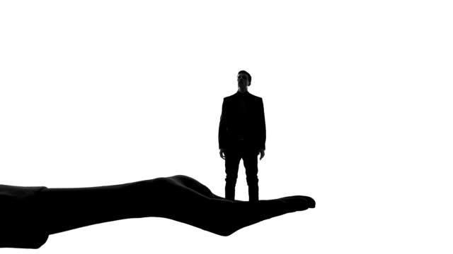 silhouette des weiblichen hand halten und zerkleinern der winzige mann, womens behörde - unterordnung stock-videos und b-roll-filmmaterial