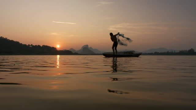 Silhouette of fishermen throwing fishing net during sunset with boats at the lake. Concept Fisherman's life style. Lopburi,  Asia, Thailand.