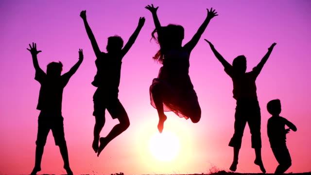 silhuetten av fem barn familj hoppning på sunrise - pink sunrise bildbanksvideor och videomaterial från bakom kulisserna