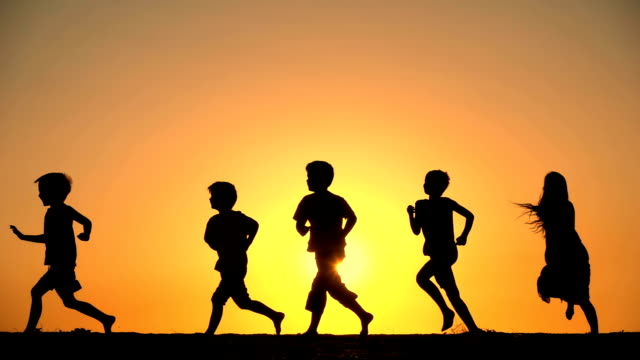 silhouette of five kids running against sunset - sagoma controluce video stock e b–roll