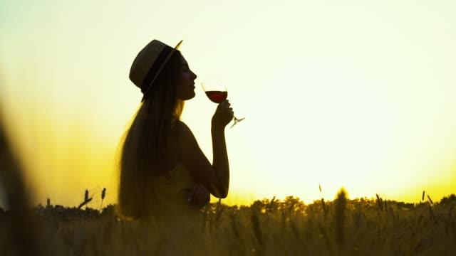 silhouette des mädchens trinken wein im weizenfeld - strohhut stock-videos und b-roll-filmmaterial