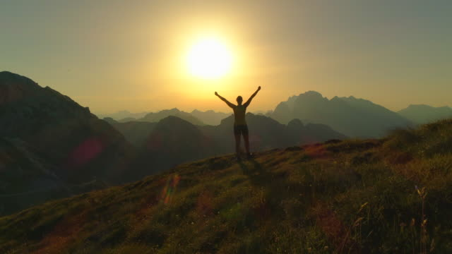 AERIAL: Silhouette of girl hiking mountains and celebrating successful ascent. AERIAL Flying over hiker woman walking up the mountain slope and raising her arms victoriously at golden summer sunset. Silhouette of girl hiking high rocky mountains and celebrating successful ascent recreational pursuit stock videos & royalty-free footage