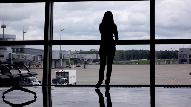 Silhouette of girl talk on phone, stand against full height window at airport Young woman silhouette against full height window, departure area of airport terminal. Girl talk on cellphone for a while then come away. Grey overcast sky, empty airport apron and taxiing area seen outside long hair stock videos & royalty-free footage