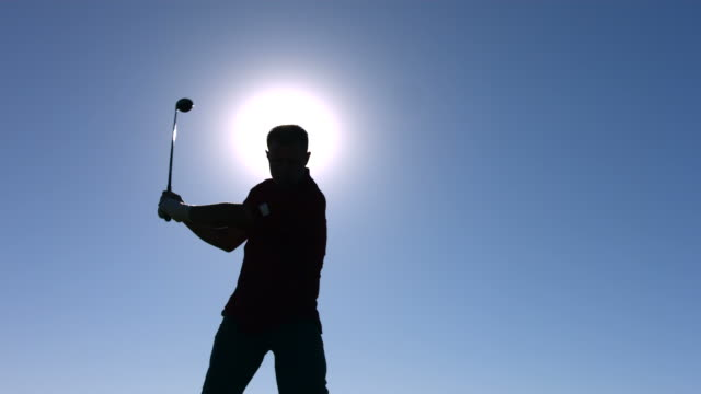 Silhouette of golfer teeing off, slow motion video