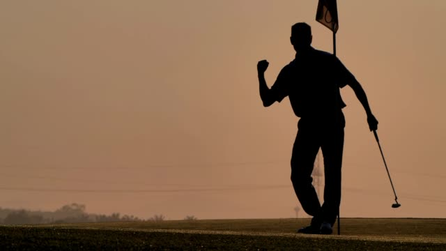silhouette der golfer treffen kehren und halten golfplatz im sommer für die entspannung. silhouette golfer bei sonnenuntergang. männlicher golfer glücklich für erfolgreichen putt auf dem grün sport cinemagraphs - golf stock-videos und b-roll-filmmaterial