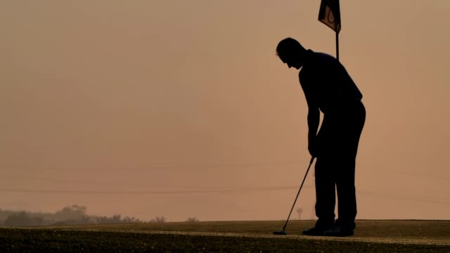 silhouette of golfers hit sweeping and keep golf course in the summer for relax time.Silhouette golfer at sunset