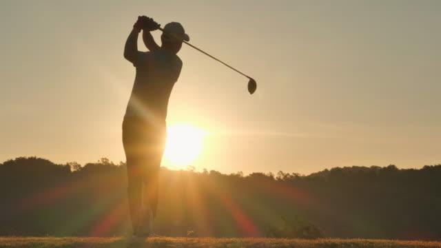 vidéos et rushes de silhouette de golfeurs frappé balayage et garder le terrain de golf en été pour se détendre. golfeur de silhouette au sunset.4k sports - golf