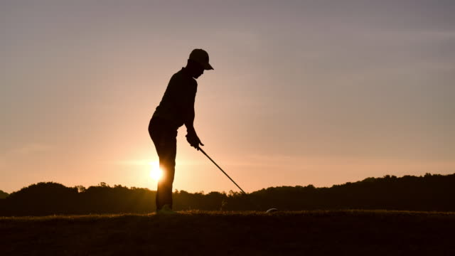 silhouette of golfers hit sweeping and keep golf course in the summer for relax time, sport concept.