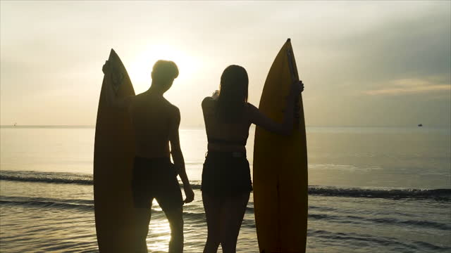silhouette of group of Asian friends running happily on the beach with surf board and jump relaxation summer vacation