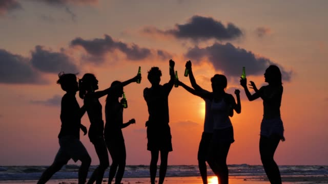 silhouette of group of friends having fun on the beach and drinking alcohol.vacations - istock - alkohol napój filmów i materiałów b-roll