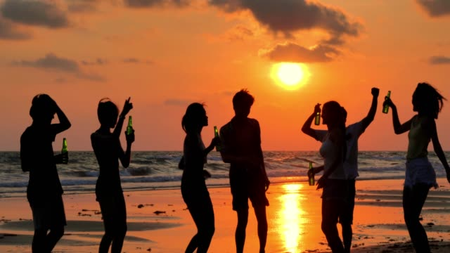 Silhouette of group of friends having fun on the beach and drinking alcohol.Vacations - iStock