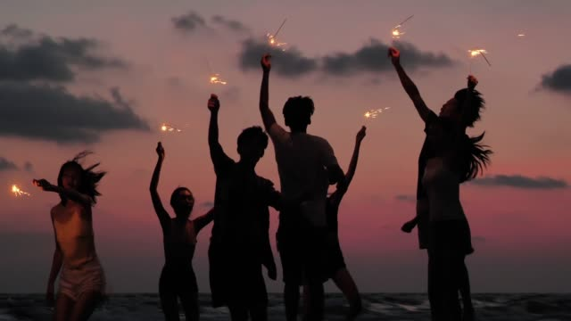 Silhouette of group of friends having fun on the beach with sparklers