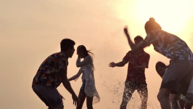 Silhouette of group of friends having fun on the beach.Slow motion.Vacations Vacations :Silhouette of group of friends having fun on the beach.Slow motion. holiday event stock videos & royalty-free footage