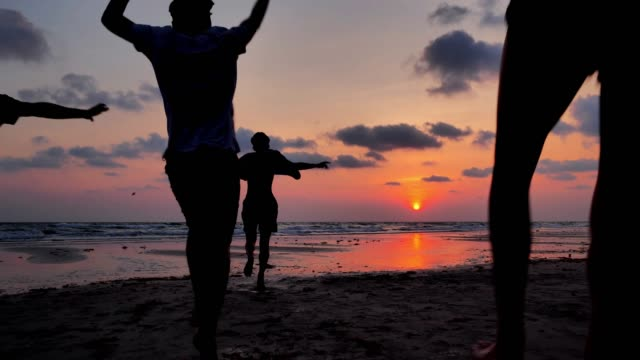 Silhouette of group of friends having fun running on the beach,Vacations - iStock video