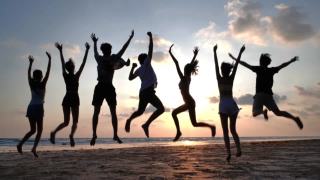 Silhouette of group of smiling friends jumping together on the beach in summer,friendship, sea, summer vacation, holidays and people concept,Vacations - iStock Silhouette of group of smiling friends jumping together on the beach in summer,friendship, sea, summer vacation, holidays and people concept beach party stock videos & royalty-free footage